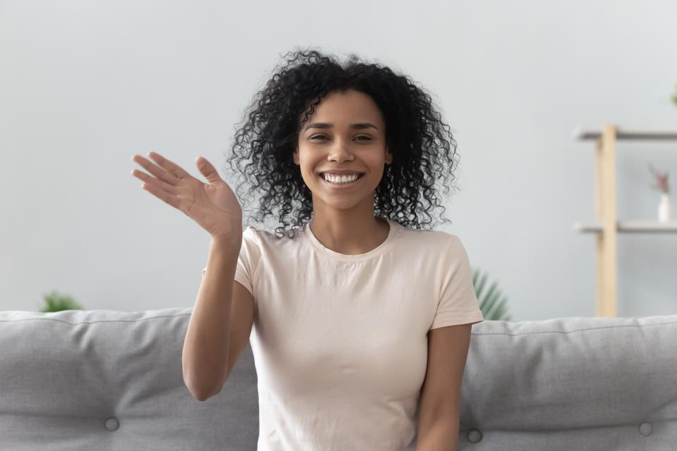 African woman feels happy wave hand looking at camera