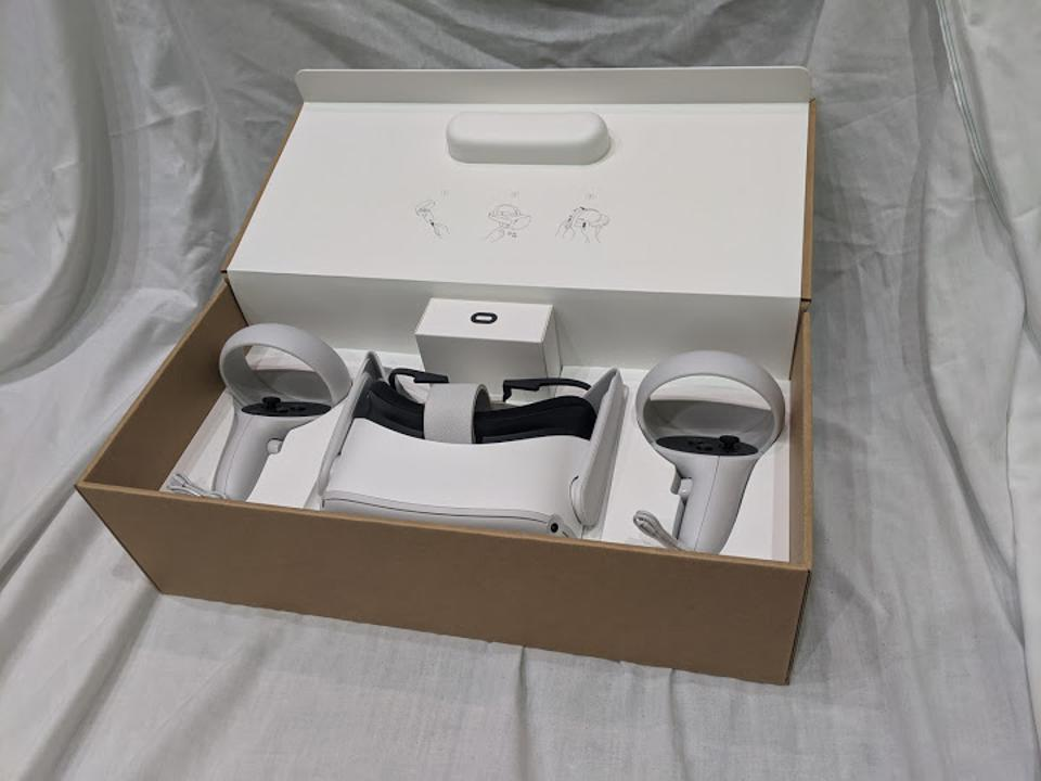 An open Oculus Quest 2 box on a white backdrop, showing the headset and controllers.