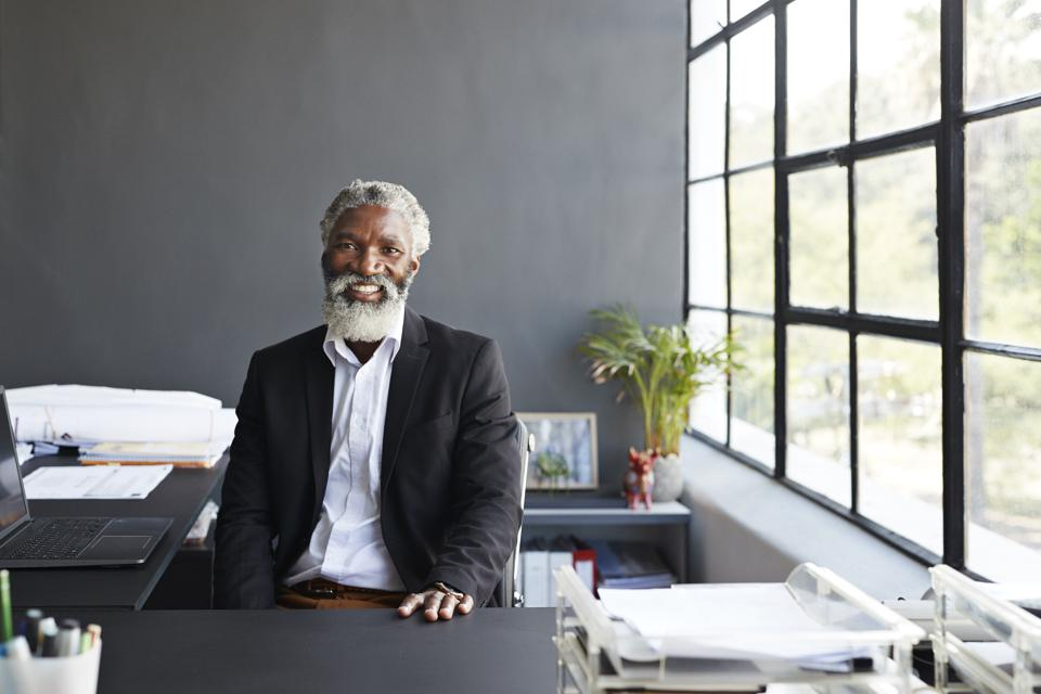 Smiling entrepreneur sitting at desk in office