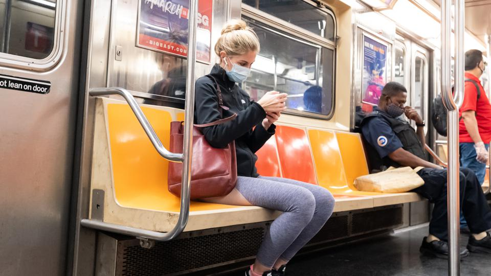 Woman sitting on subway with mask.