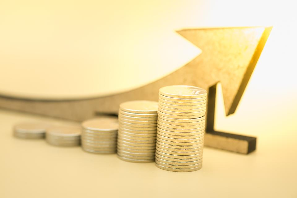 Money, business, saving and growth concept. Close up of stack of silver coins with wooden arrow symbol.