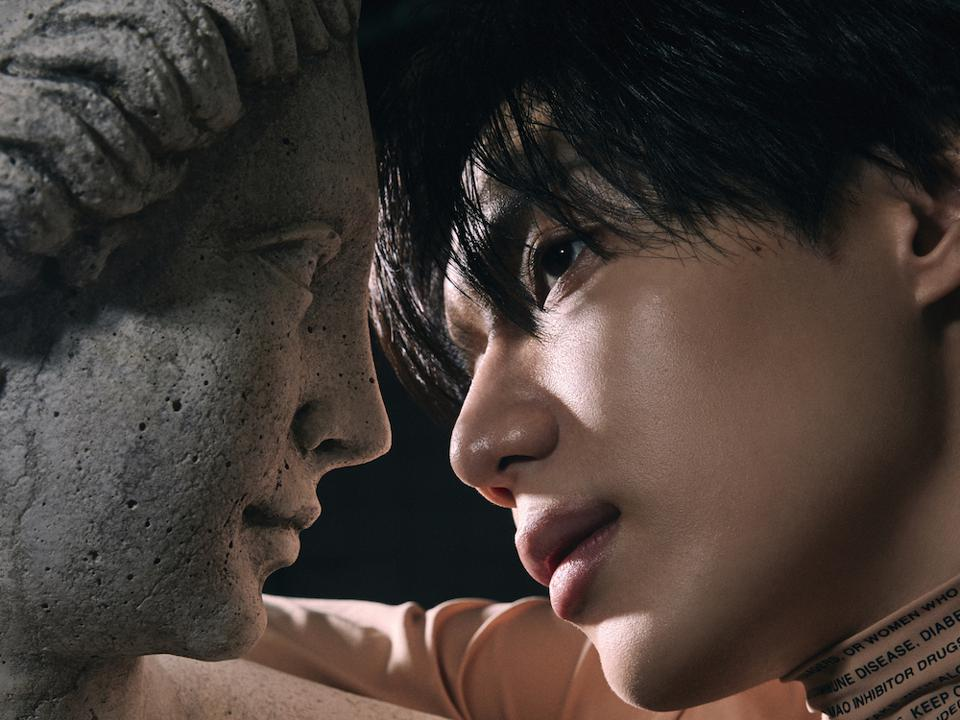 Taemin leaning into caress with classic-looking sculpture bust