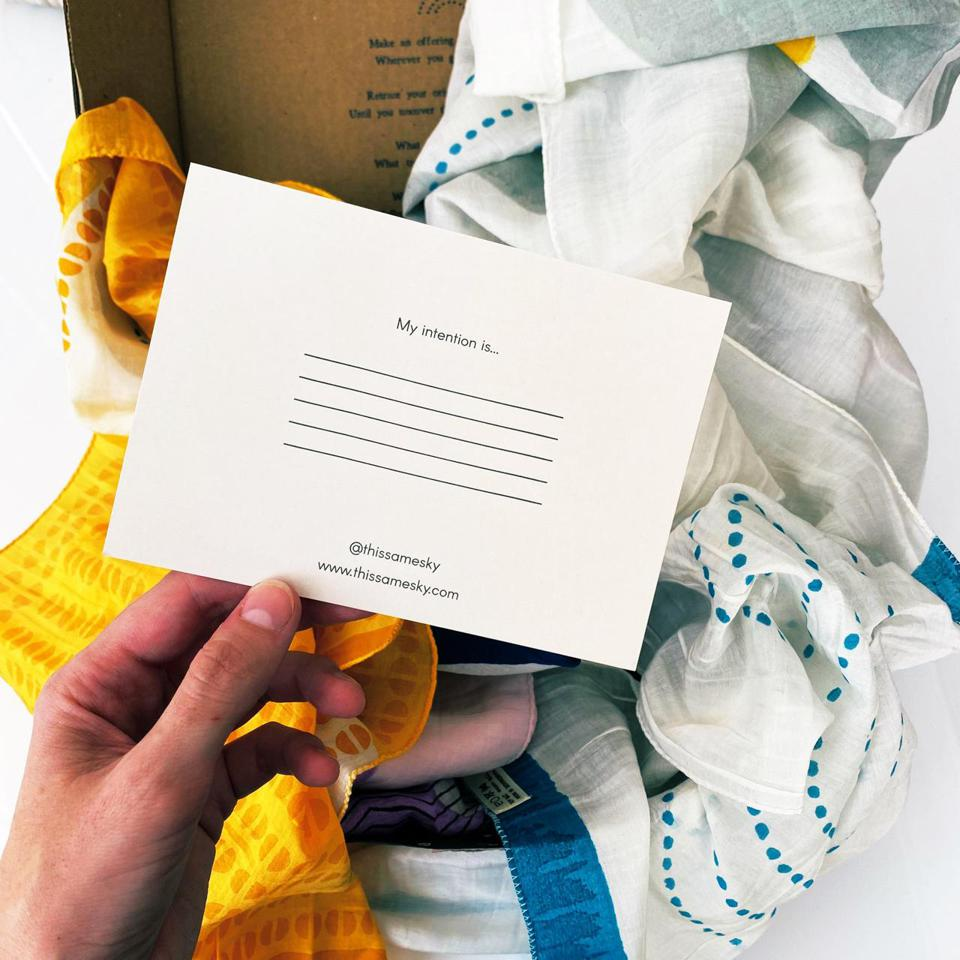 A note card saying ″My intention is″ against background of a white and blue scarf