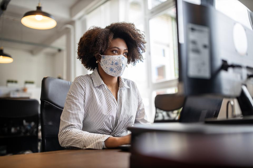 Businesswoman with face mask working at her desk.