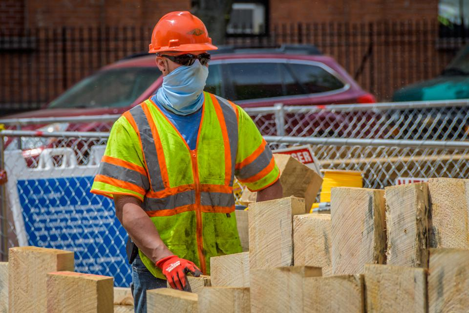 Construction workers wearing protective face masks on site.