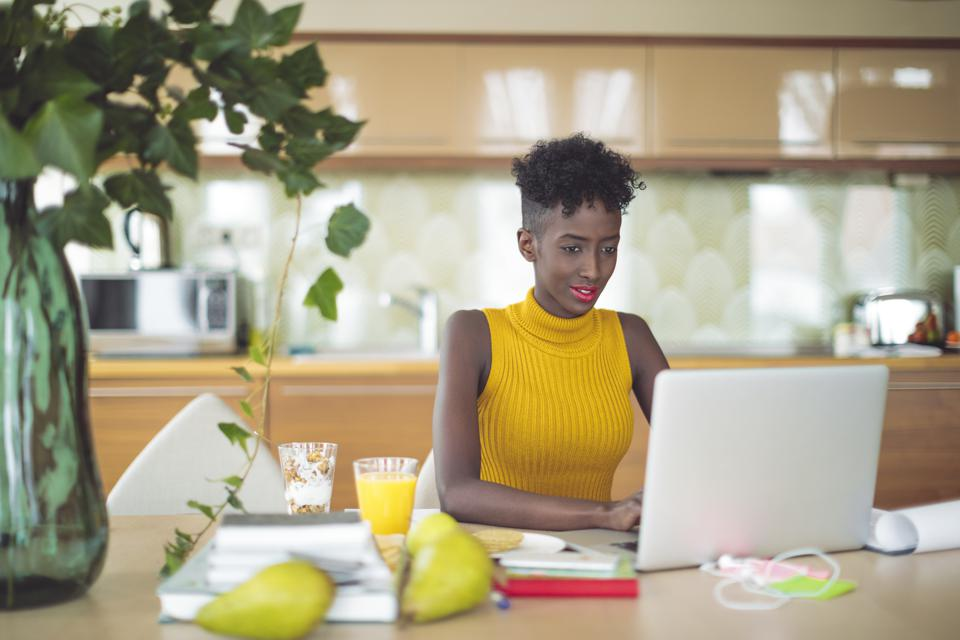 Young woman is working at home on her laptop