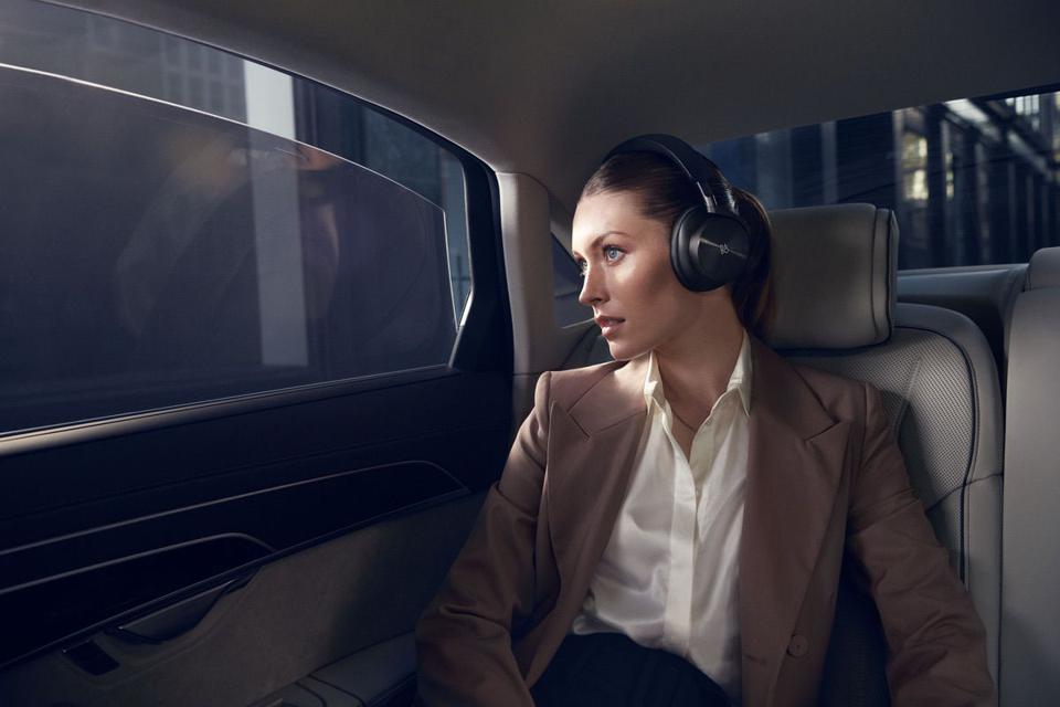 Woman in back seat of car wearing Beoplay H95 headphones
