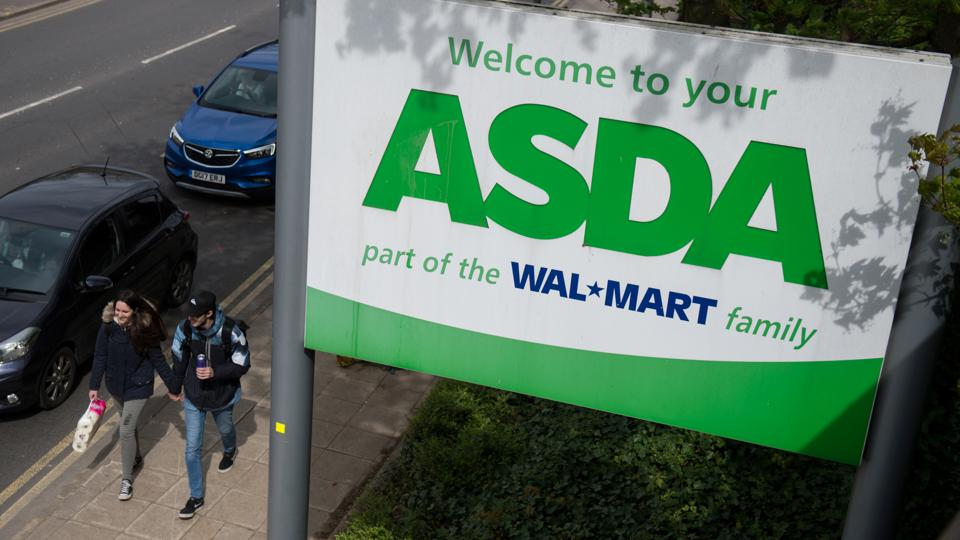 Asda sign with Walmart logo and a couple walking past.