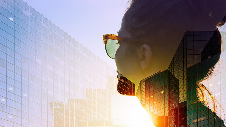 Woman with sunglasses, glaring sun and modern office buildings.