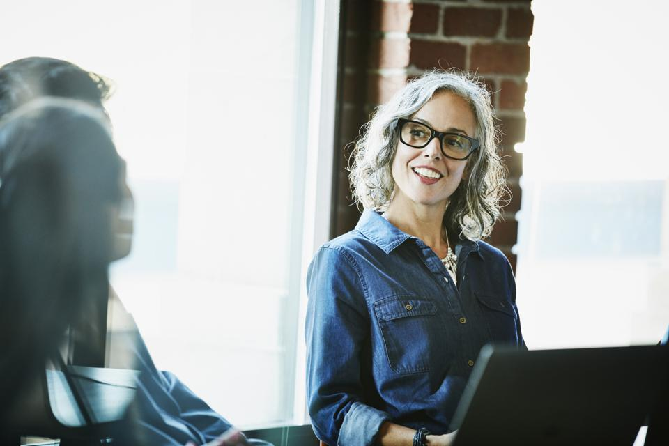 Smiling businesswoman leading meeting with clients in conference room