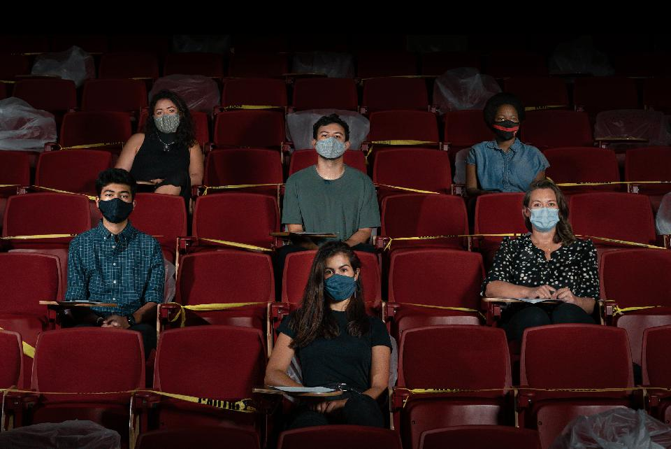 Masked students sitting four seats apart in a dark lecture hall