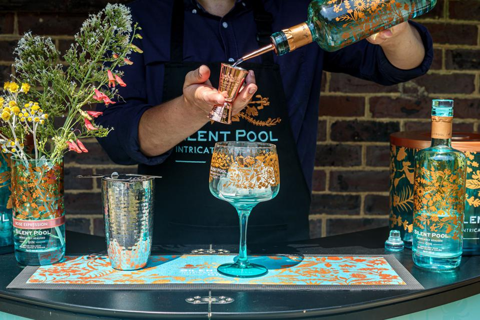 Barman pouring high-end gin into a shaker.