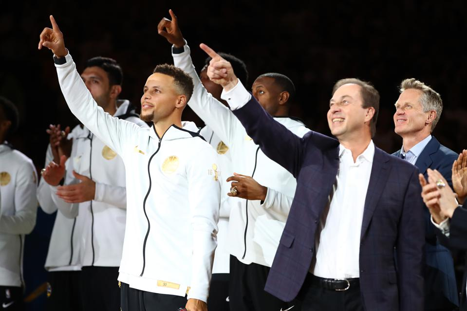 Joe Lacob, Stephen Curry, and Steve Kerr point to the 2017 championship banner.