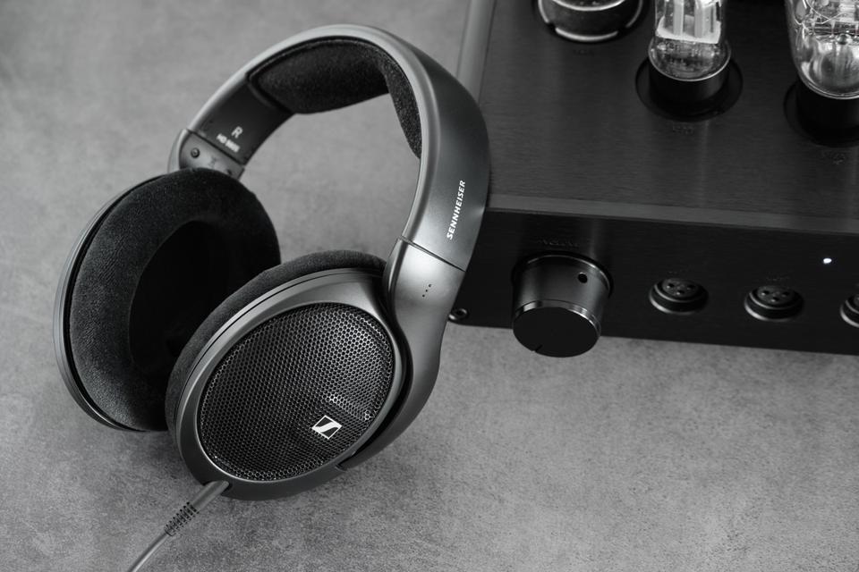 A pair of Sennheiser HD 560S earphones next to an amplifier
