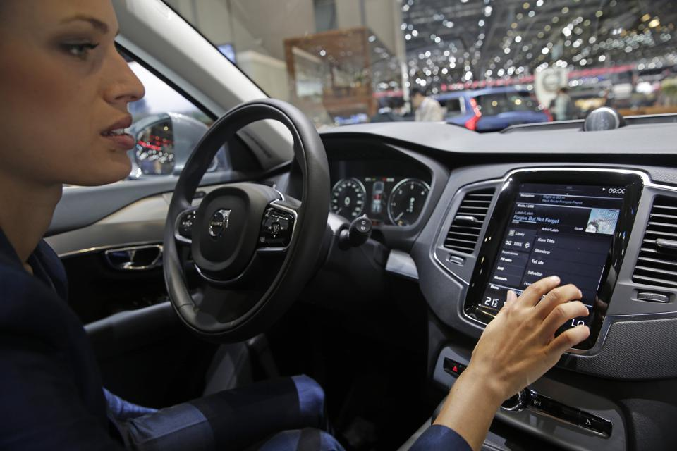 An employee demonstrates the touch-screen display of a Volvo XC-90 automobile