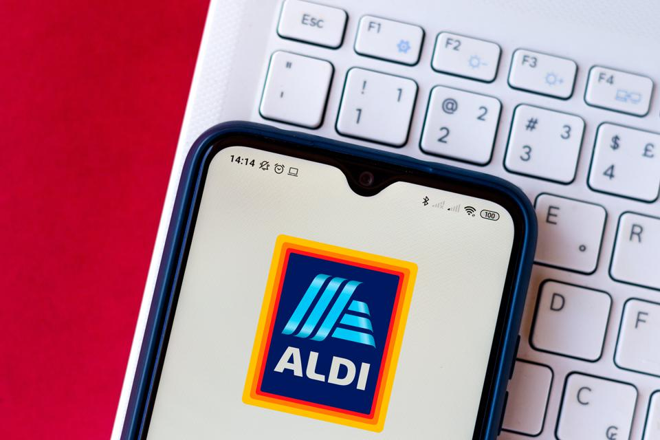 In this photo illustration, an ALDI logo seen displayed on a smart phone with a keyboard behind it