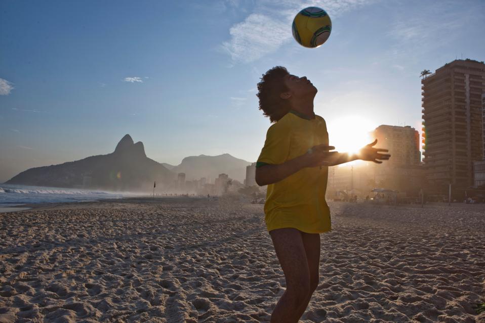 Young man heading football, Ipanema Beach, Rio, Brazil