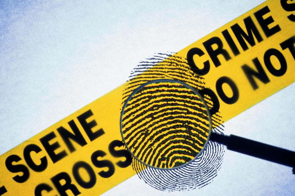 Police crime scene tape with fingerprint under magnifying glass illustrates a story about dumb hacker uploading fingerprints to the scene of a cybercrime
