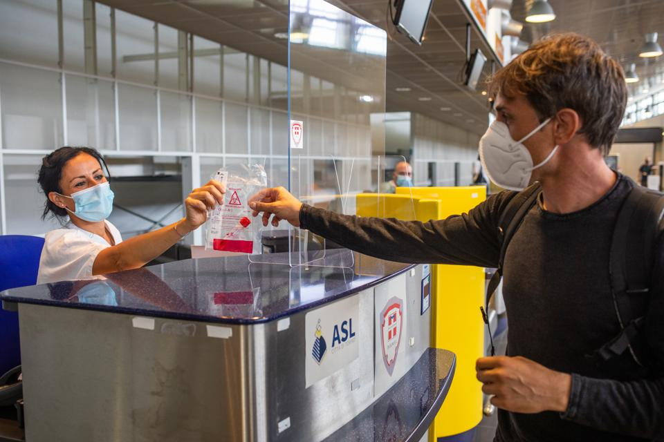 A traveler receives test tubes to carry out a Covid-19 swab test, in Turin, Italy.