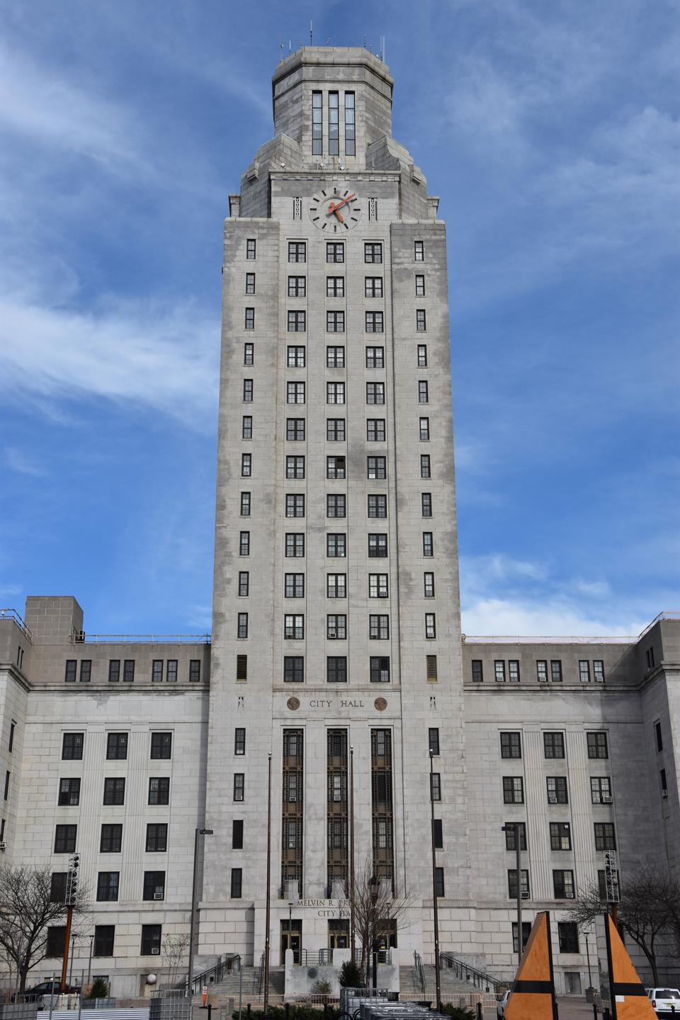 City Hall building with large footprint, and a clock tower rising in the center