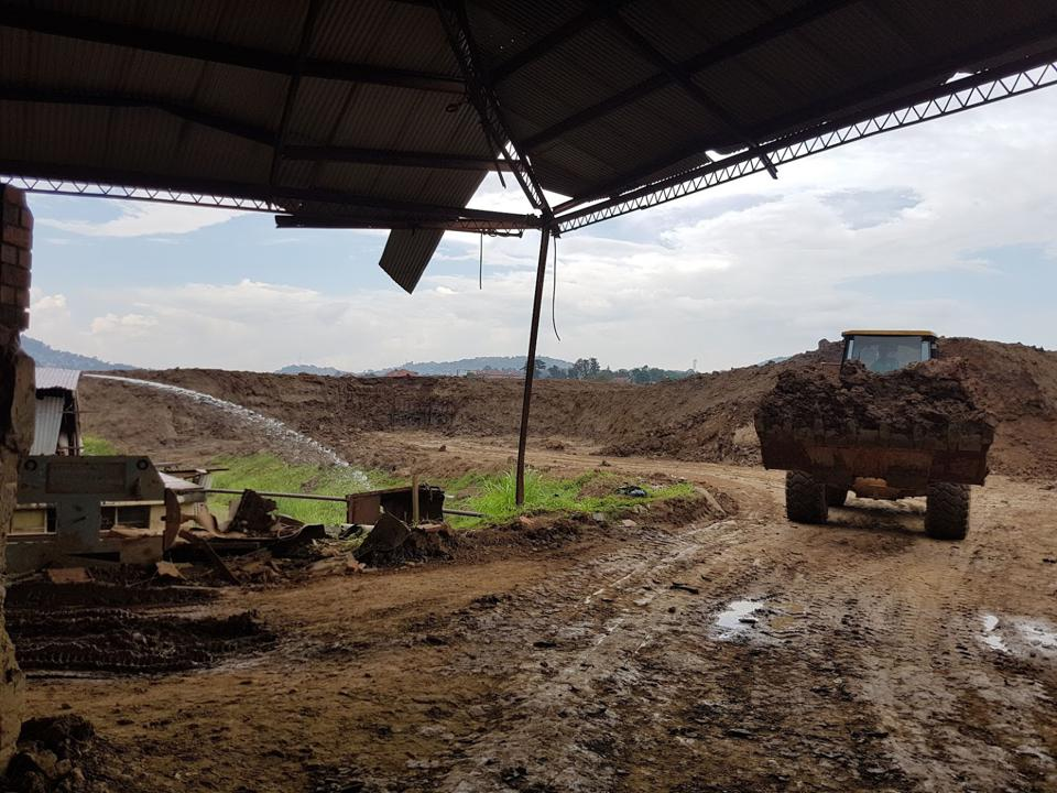 Excavator rumbles towards the viewer with a large pile of clay