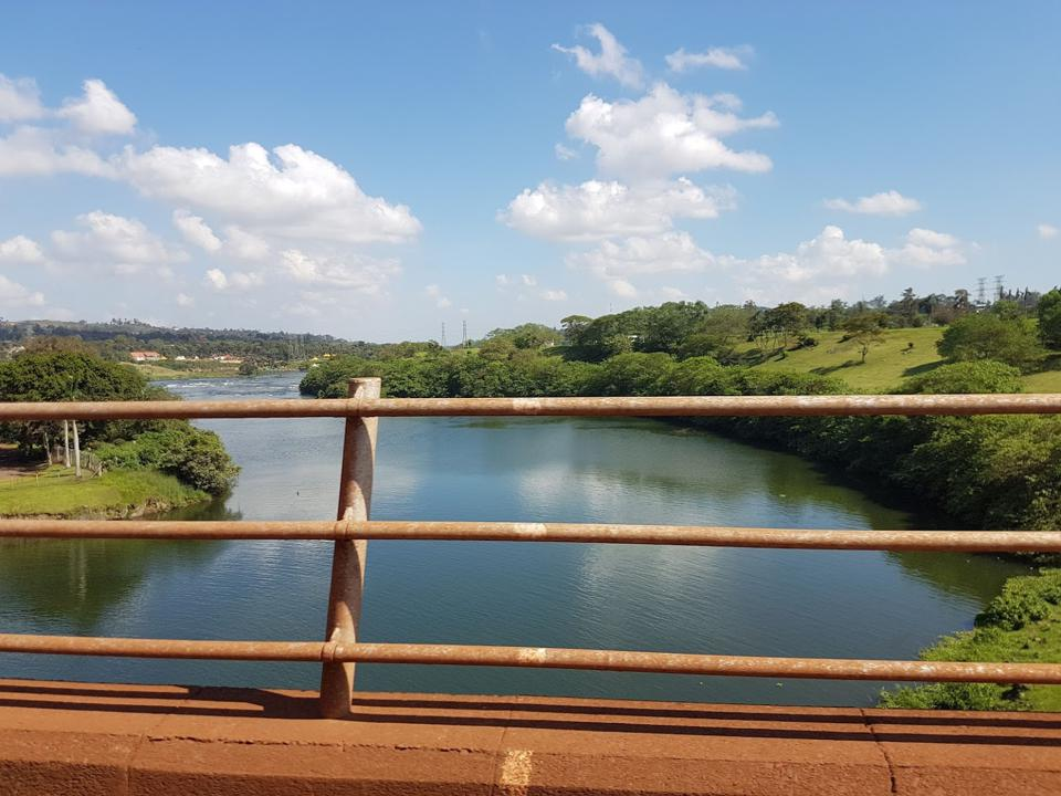 Looking out over a tree lined, grassy river valley with a bridge railing in the foreground