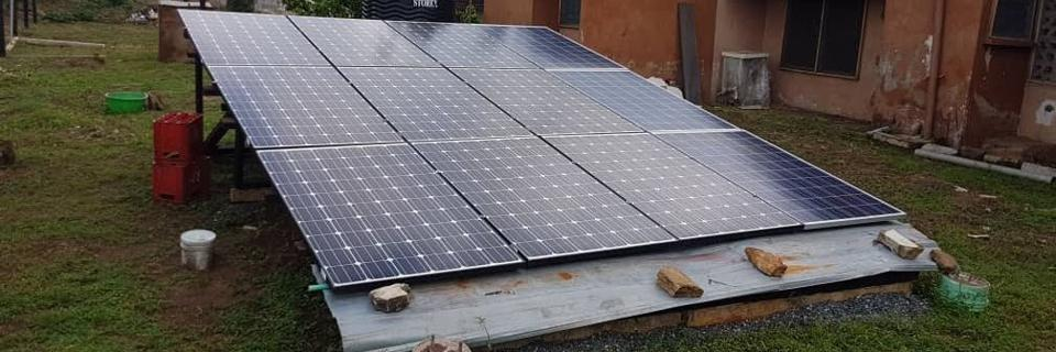 Six solar pv panels line a ground mounted generation array in a residential garden