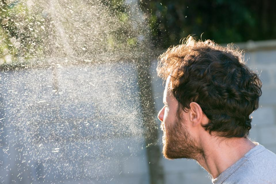 Man sneezing spray cloud Coronavirus transmission germs