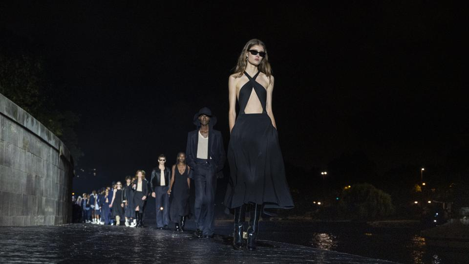 A line-up of models in Ami's Spring Summer 2021 collection in shdes of blue, black and denim n final show walk. The first model wears a  crisscross halter to and skirt