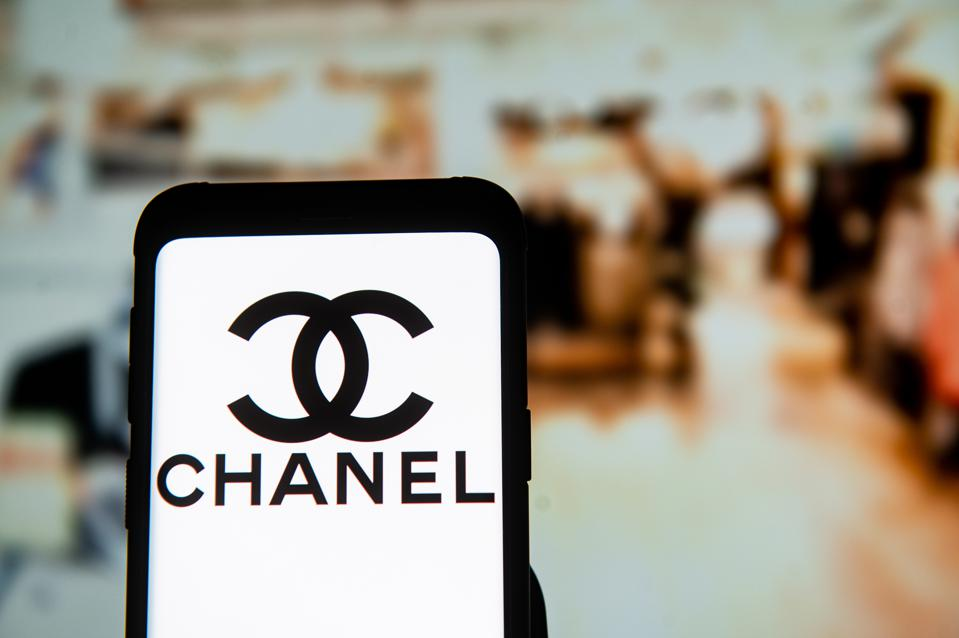 In this photo illustration a Chanel logo seen displayed on a...