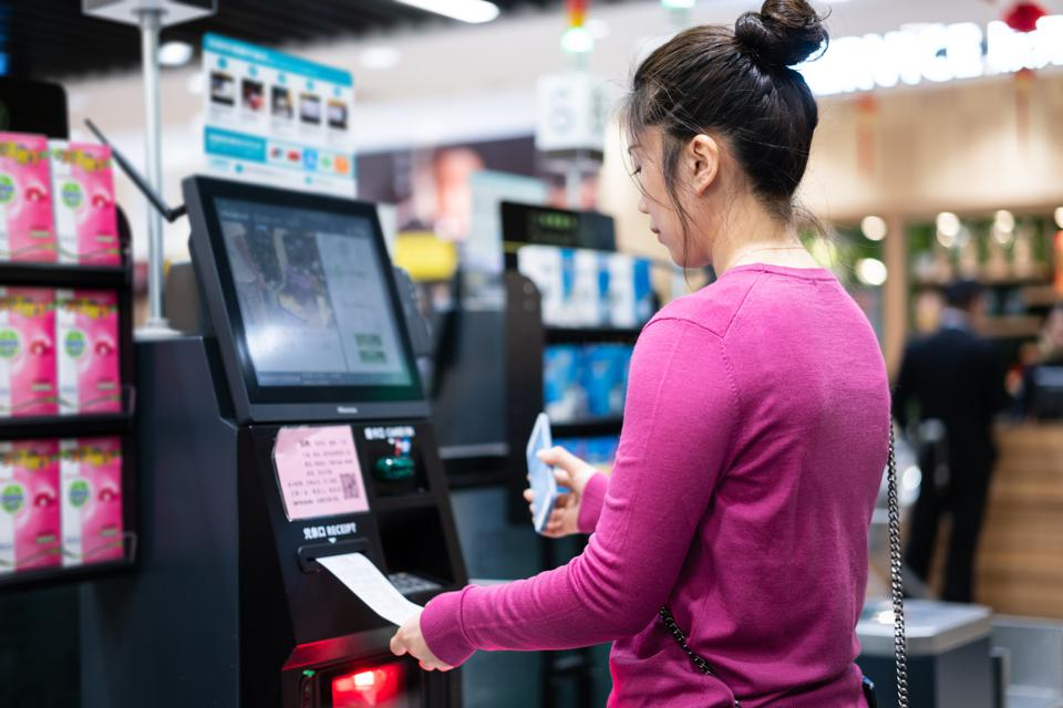 asian female contactless payment on automatic payment machine in supermarket