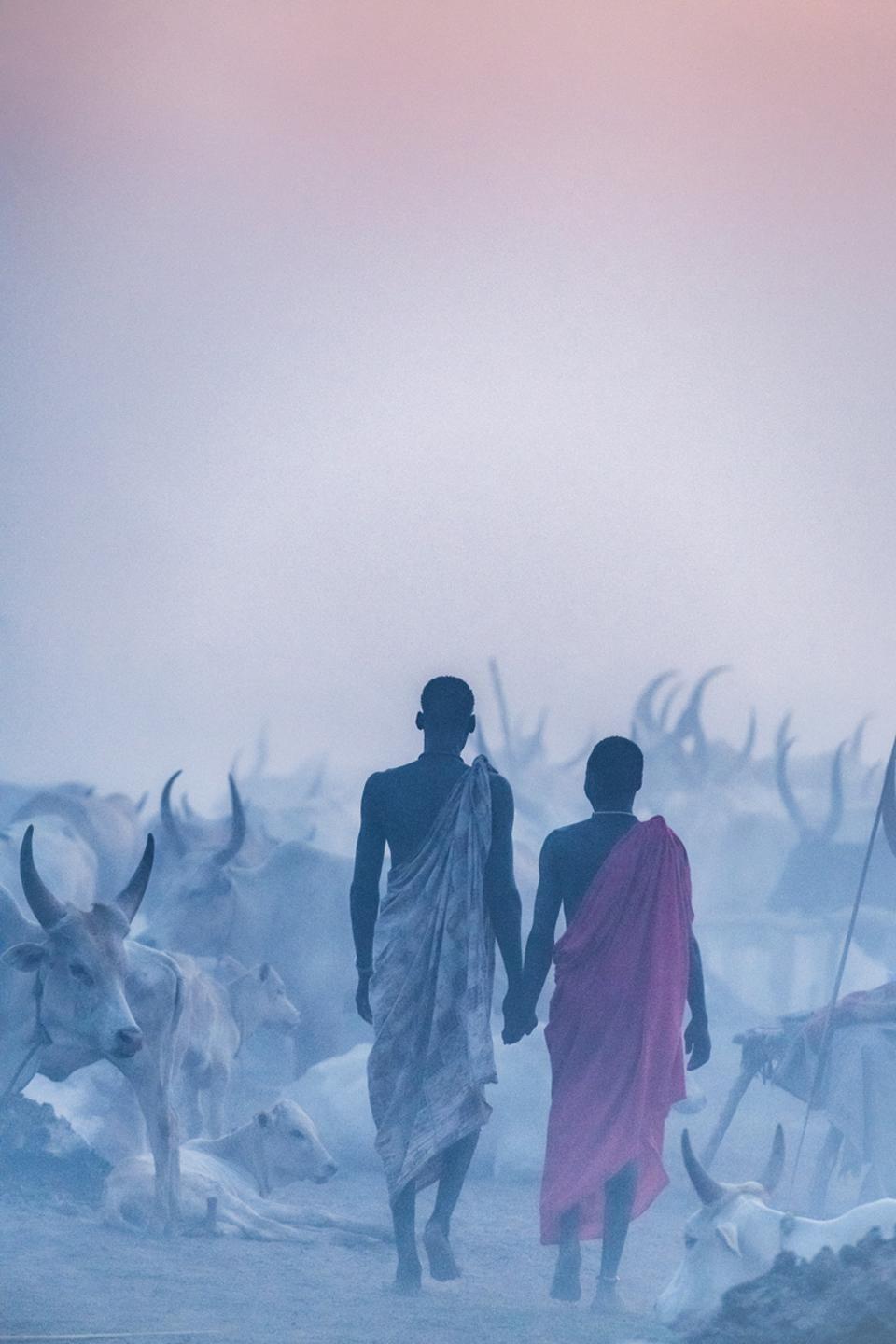 Two Mondari herders in Sudan, walk hand in hand into the dusk and dust in the blue hour.