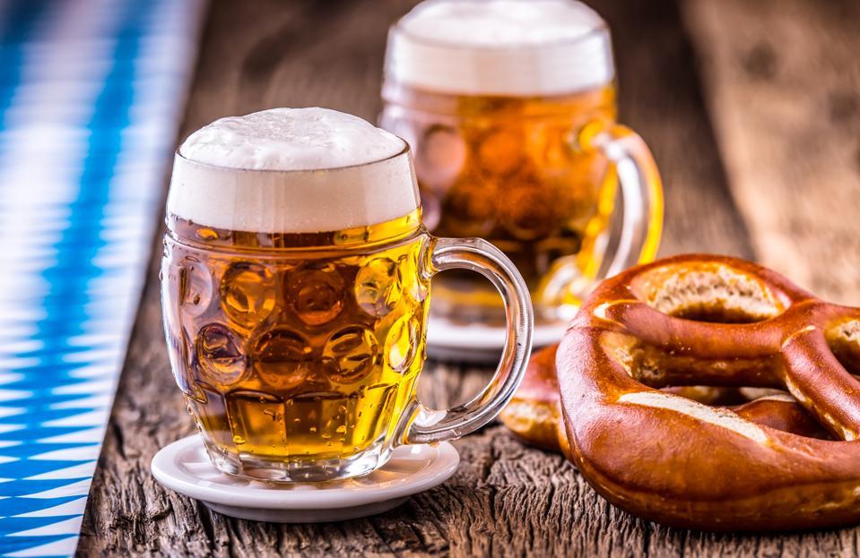 Beer. Oktoberfest.Two cold beers and pretzel. Draft beer. But draft. Golden beer. Golden however. Two gold beer with froth on top. Cold draft beer in glass jars in a hotel pub or restaurant. Still life