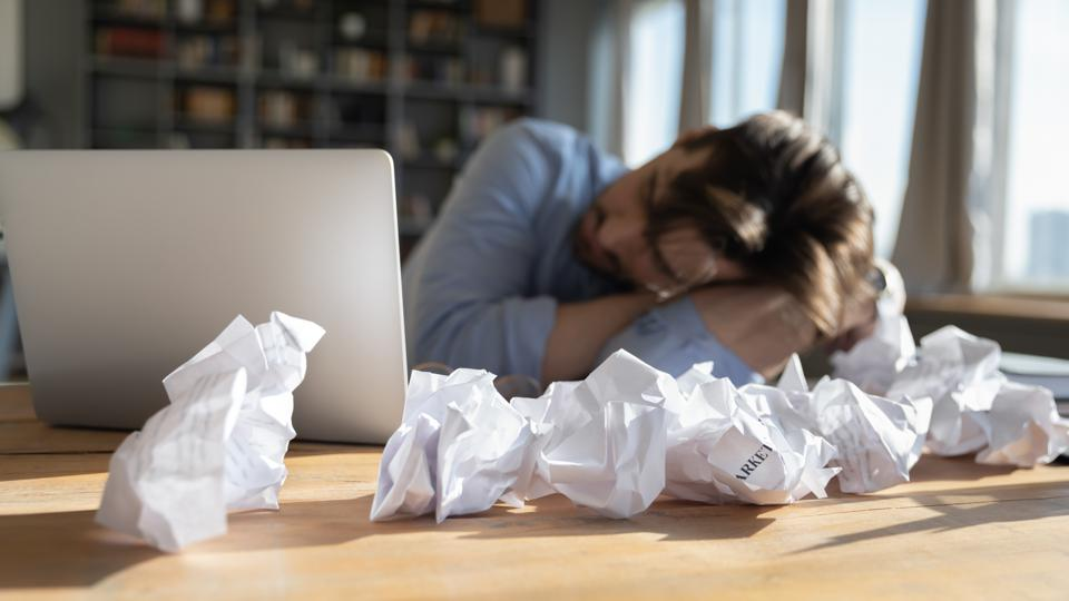Tired overworked businessman sleeping at desk covered crumpled papers