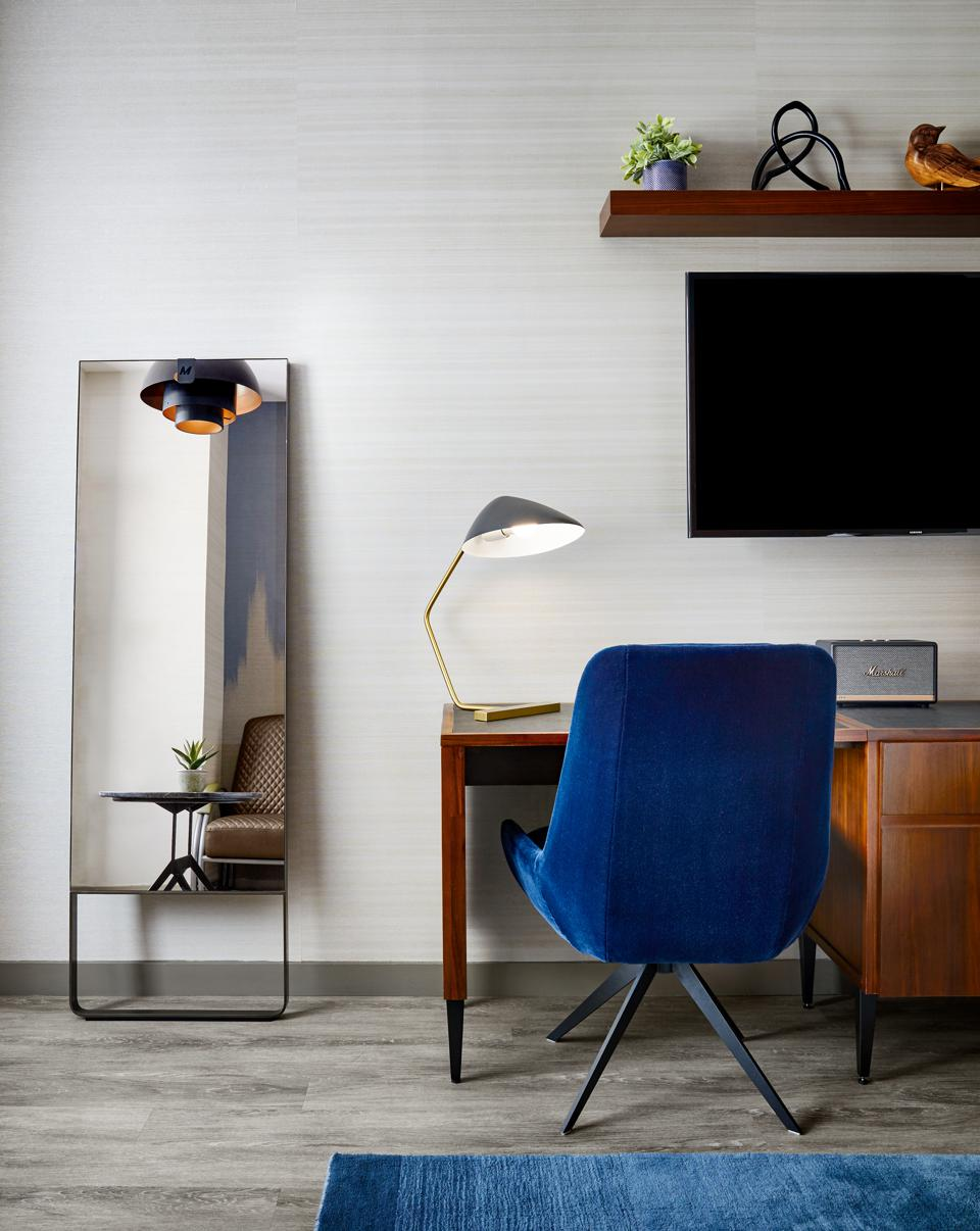 Chic office space with the mirror and matching blue velvet chair and carpet