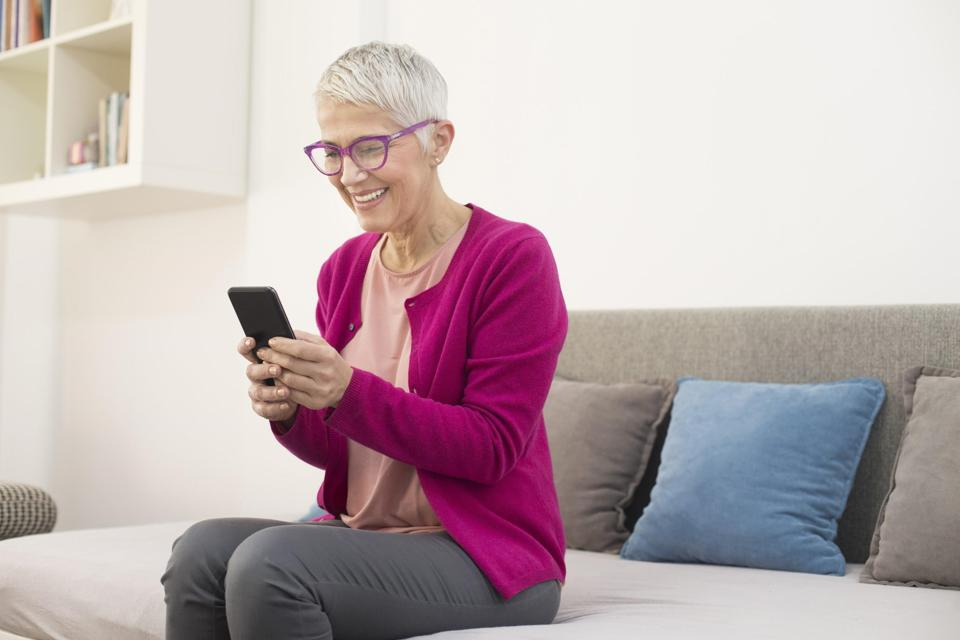 woman sitting on couch using phone