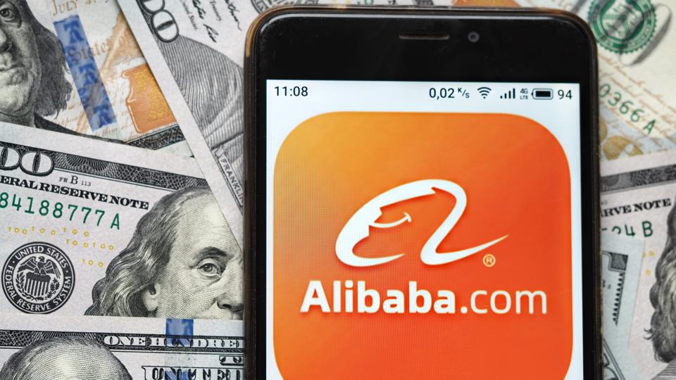 photo illustration an Alibaba logo seen displayed on a smartphone with 100 dollar bills in the background