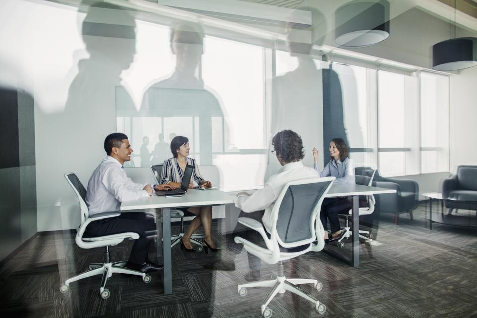Team talking together in business meeting room