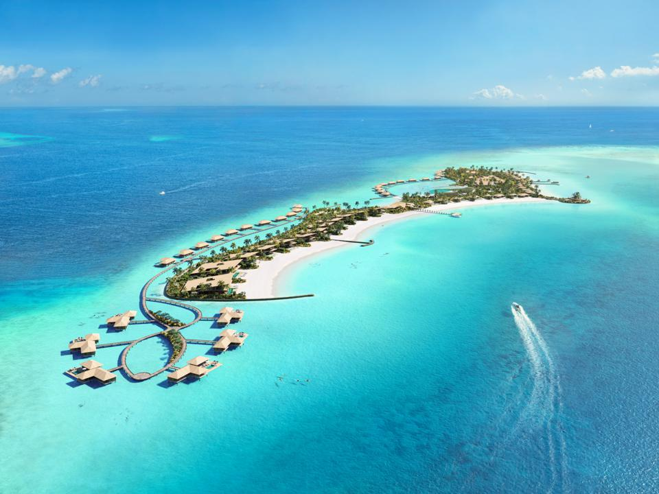 A string of overwater villas in turquoise water