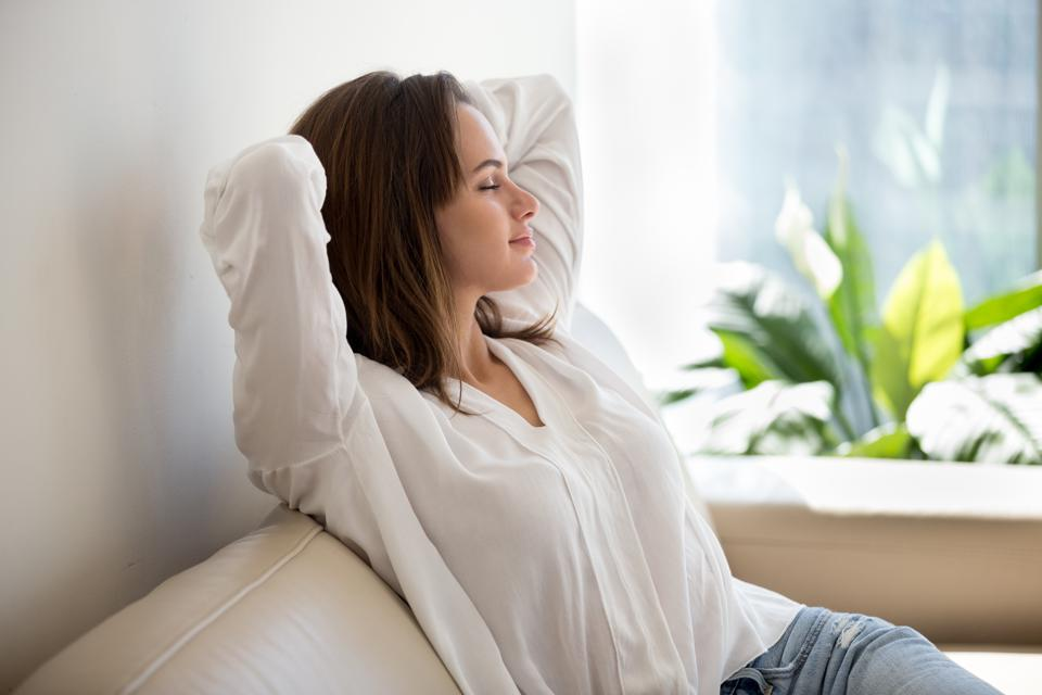 Relaxed woman resting breathing fresh air at home on sofa