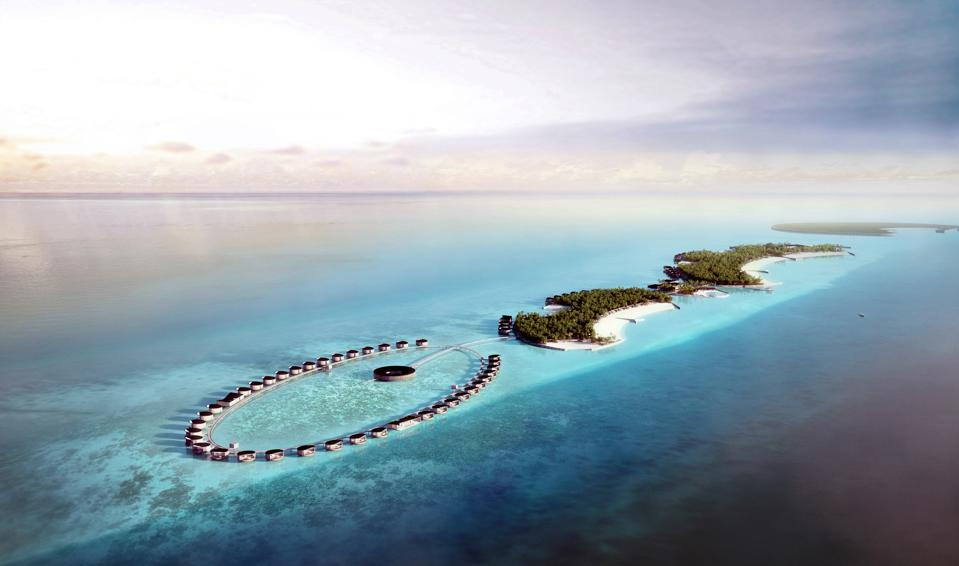 An oval string of overwater villas surrounded by turquoise water