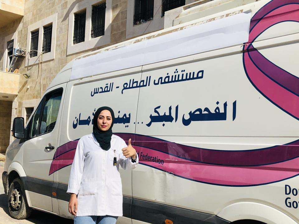 Elham Edaes - stands by a van - with thumbs up