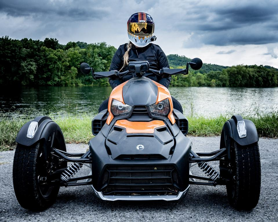 A woman sits atop a Can-Am Ryker, a three-wheeled motorbike.