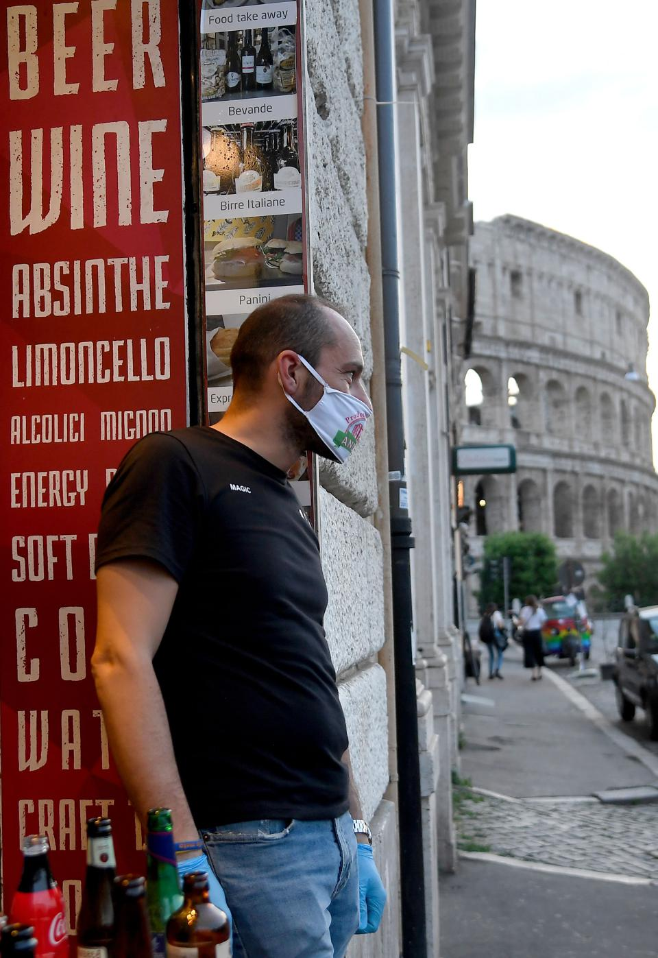 Man wearing a mask outside a cafe bar near Italy's Rome Colosseum