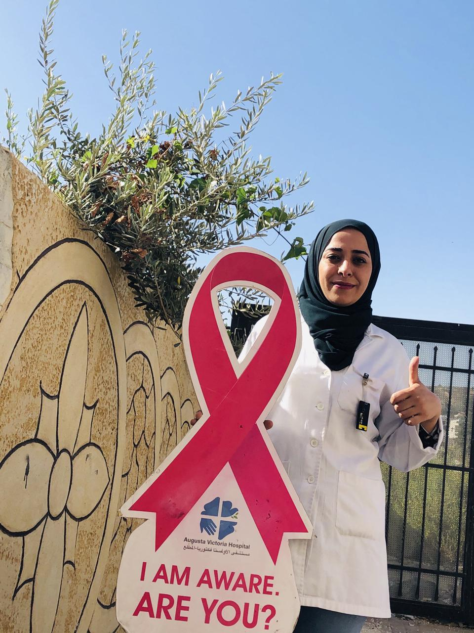 Elham Edaes holding breast cancer awareness sign