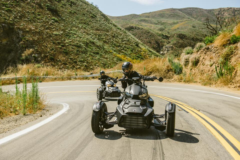 Two black trikes whip around a tight bend at speed in the California hills.