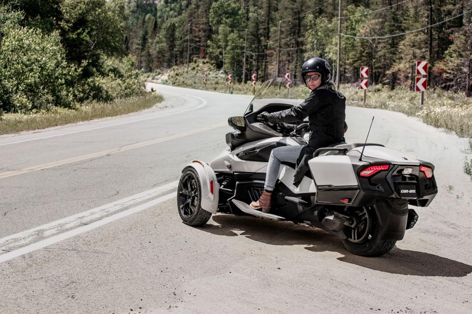 A woman rides a Can-Am Spyder on the side of a highway.