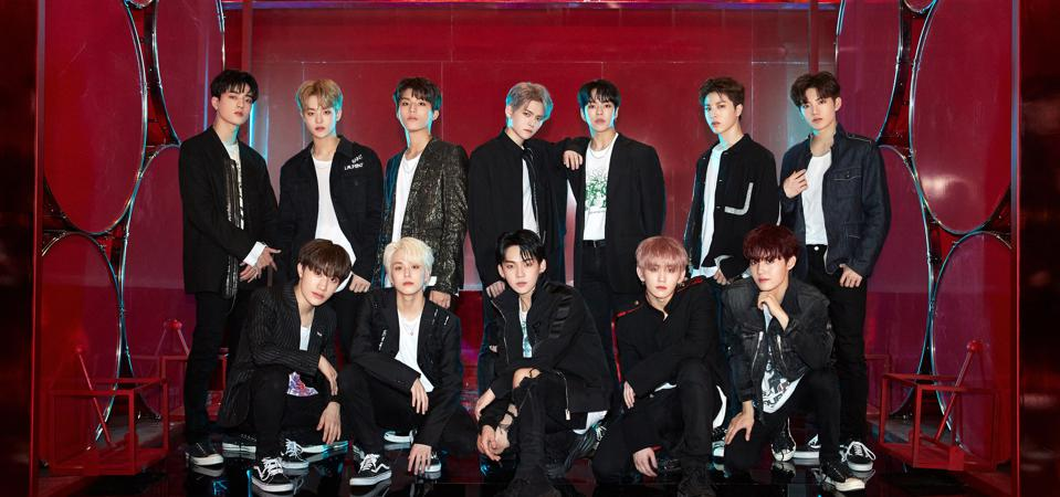 The 12 members of Treasure posing in black and white outfits in front of a red set