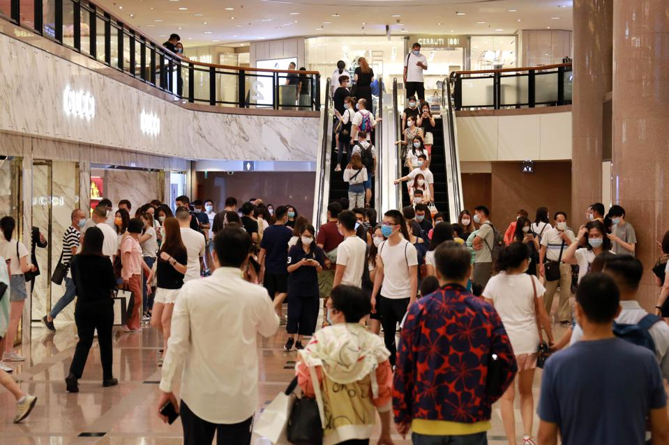 Throng of masked crowds fervently shopping at Harbour City, the largest mall of Hong Kong.