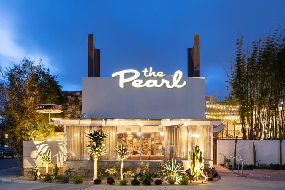 The exterior of The Pearl Hotel at dusk.